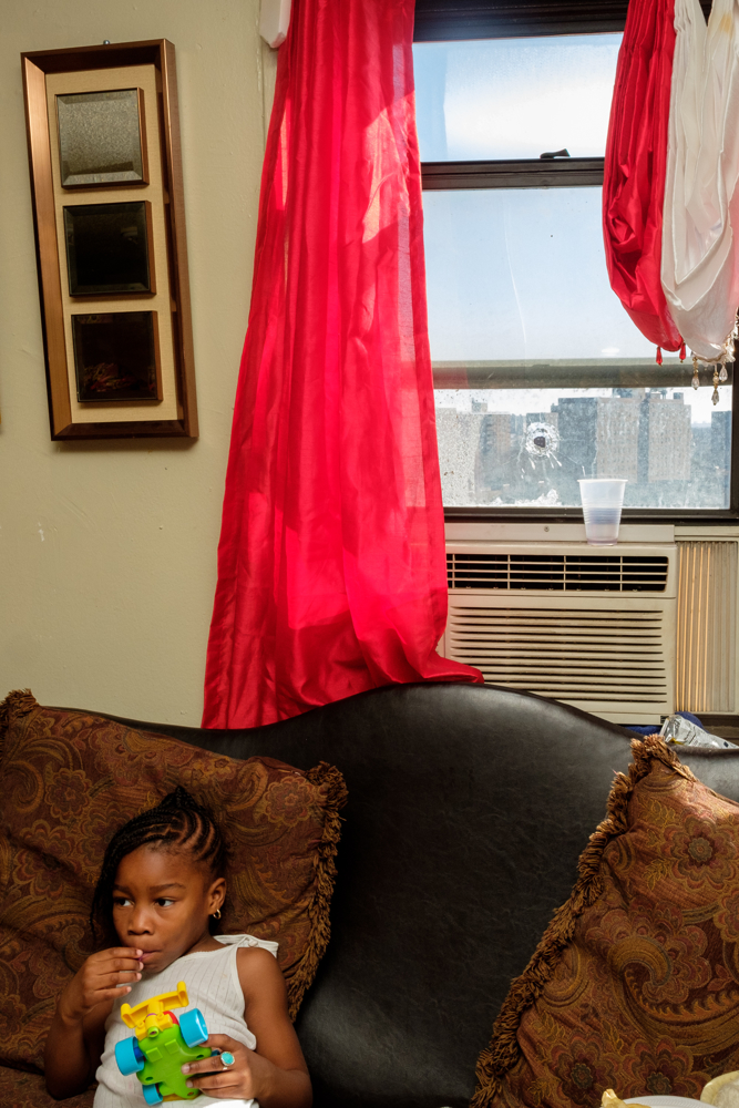 A young relative of Luis Diego sits on New Years Day with a bullet hole in the window.  Diego, 46, was hit in the arm by a stray bullet on the 12th floor of a building in the Langston Hughes Houses on Sutter Ave. in Brooklyn while embracing family and friends at 12:01 after New Years Eve.