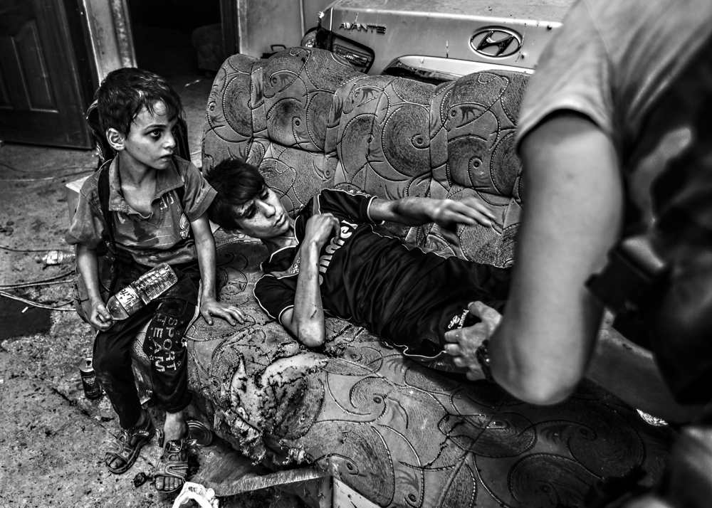 A child is triaged from a knee injury sustained from a mortar explosion as he and his family flee Mosul's Old City on June 30, 2017. A day after the Iraqi government declared the Islamic State was defeated in Mosul, heavy fighting persisted while newly liberated residents still fled the Old City neighborhood in droves. With temperatures reaching 115 degrees, many needed medical attention for heat exhaustion.