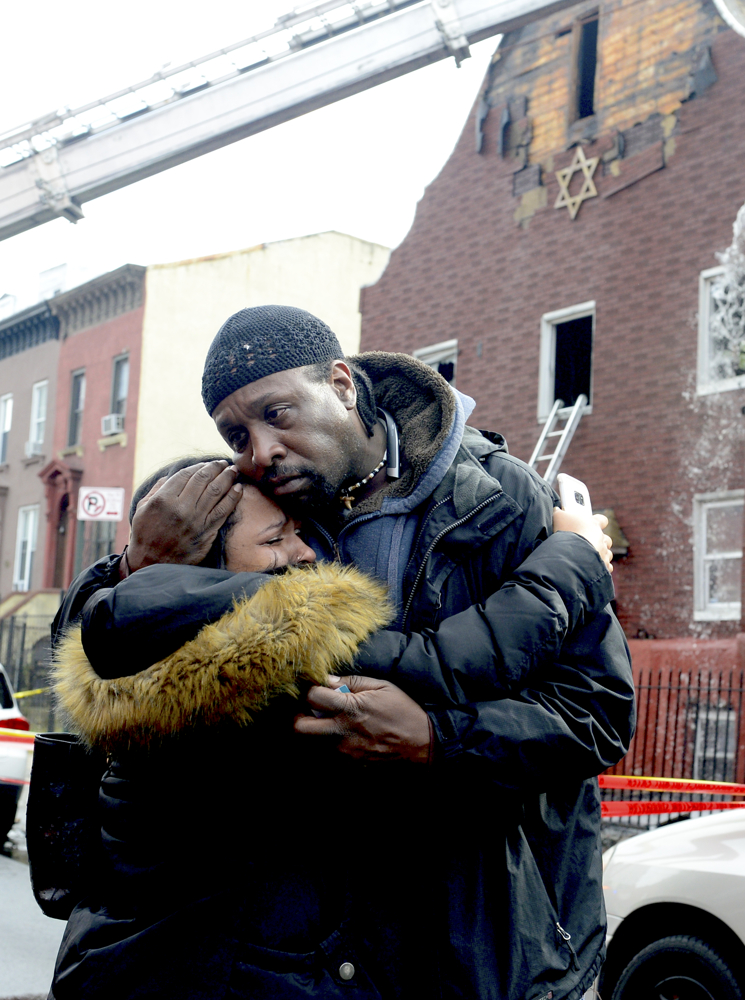 Rabbi Baruch Yehuda embraces a woman named Flowers, at the synagogue fire. A massive synagogue fire, B'nai Adath Kol Beth Israel, tore through the 200 year old structure at Patchen Avenue and Greene Street in Bed Stay Brooklyn November 14, 2017. No serous injuries.