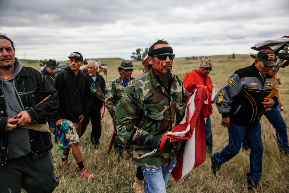 September 15, 2016: Cannonball, ND - Protesters carry an American flag to a Native American burial site to perform a ceremony. Hundreds gathered to form a protest camp named Oceti Sakowin, led by the Standing Rock Sioux tribe to protest the Dakota Access Pipeline.