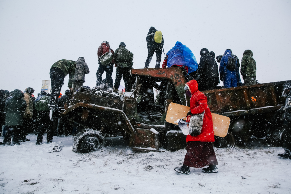 December 5, 2016: Cannonball, ND - Protesters climb a burned out truck while marching with US military veterans visiting to show solidarity with the Oceti Sakowin camp. Hundreds gathered to form a protest camp named Oceti Sakowin, led by the Standing Rock Sioux tribe to protest the Dakota Access Pipeline.