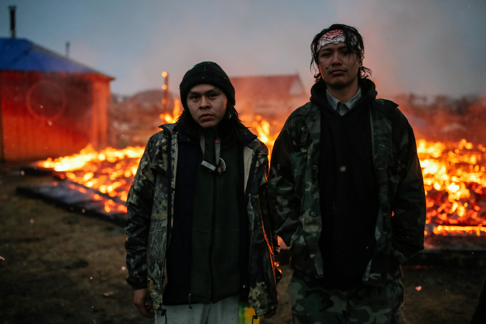 February 22, 2017: Cannonball, ND - Chanse Zavalla, 22, left, and O'Shea Spencer, 20, in front of a structure set on fire by campers in anticipation of a raid by law enforcement at the Oceti Sakowin camp. Led by the Standing Rock Sioux tribe to protest the Dakota Access Pipeline, the camp was dismantled by authorities the next day.