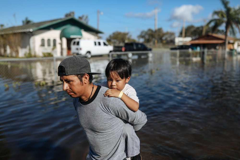 September 12, 2017: Immokalee, FL - Wilson Perez carries his son, Jose Miguel Perez, 4, after their street was flooded by hurricane Irma. The town of Immokalee, home to migrant farm workers and immigrants from Haiti and Latin America, was one of the hardest hit by the category 5 storm.
