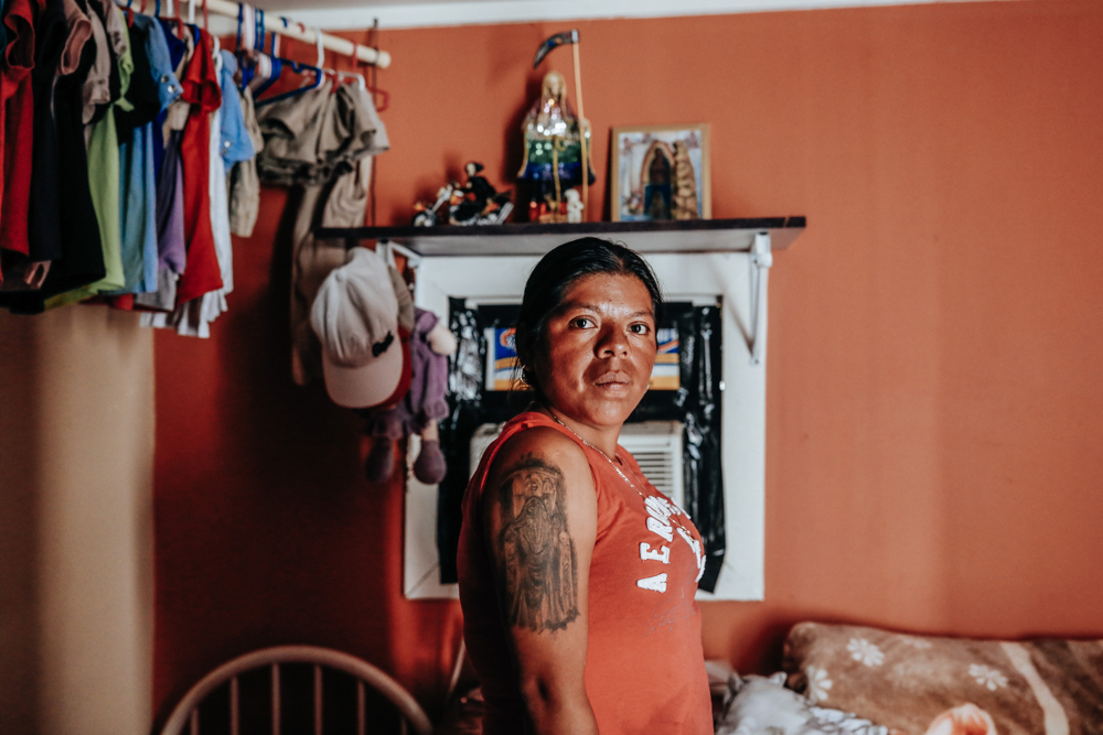 September 25, 2017: Immokalee, FL - Sandra Guzman shows her tattoo of Death in front of a shrine in her temporary home after her trailer home was destroyed by hurricane Irma. The town of Immokalee, home to migrant farm workers and immigrants from Haiti and Latin America, was one of the hardest hit by the category 5 storm.