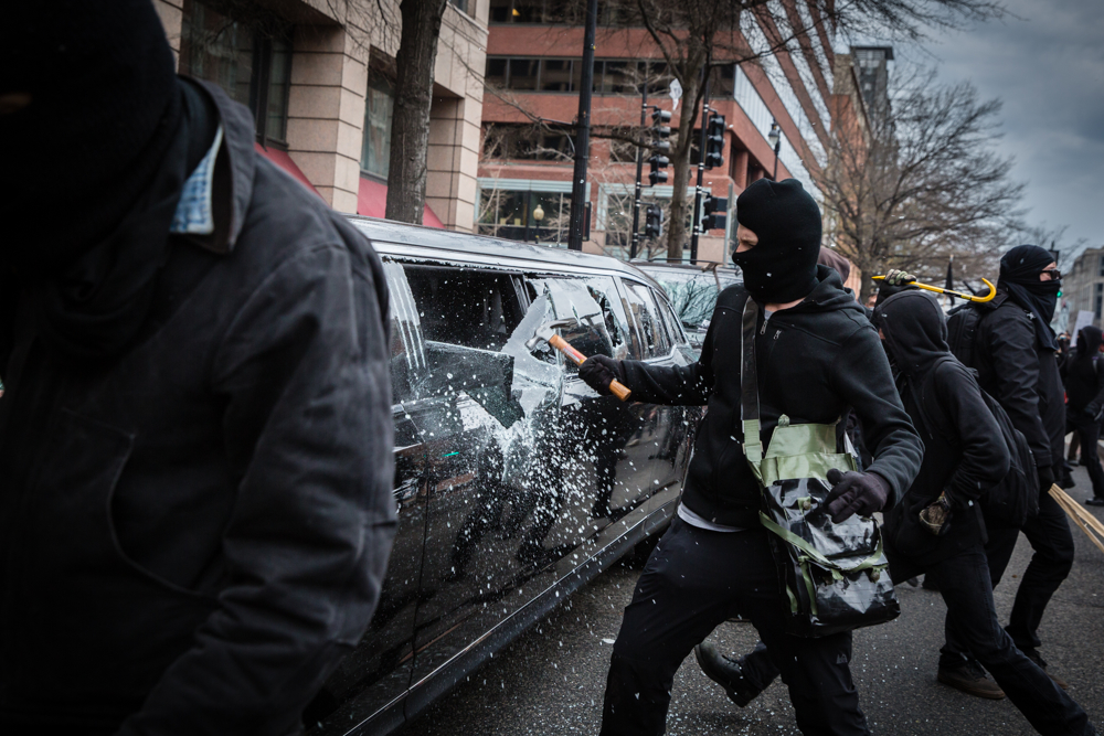 A Black Bloc anarchist protestor smashes the windows of a limousine with a hammer during the mayhem on Inauguration Day near Franklin Square on January 20, 2017 in Washington, DC, USA.