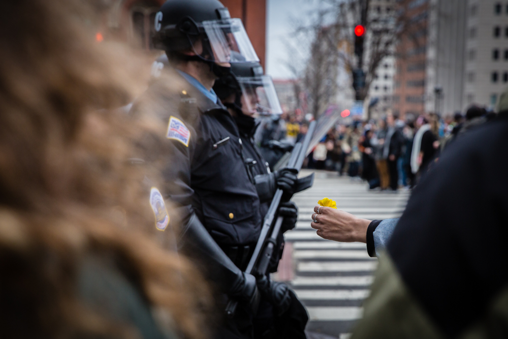 A woman offers a flower to the riot police during the mayhem on Inauguration Day near Franklin Square on January 20, 2017 in Washington DC, USA.