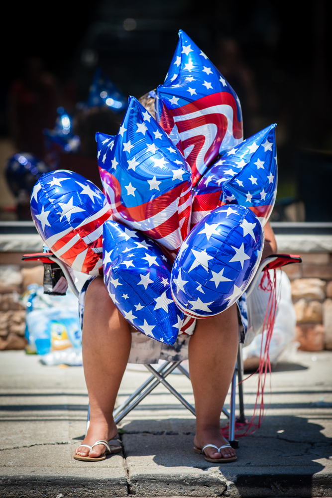 A woman is swallowed up by a bundle of balloons at the 4th of July Independence Day Parade in Travis, Staten Island on July 4, 2017 in New York City, USA.