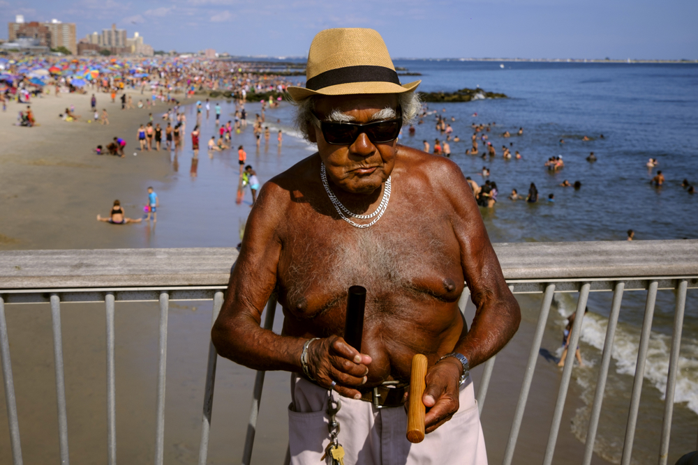 Tanned and Rested - While on the pier, Alberto plays the percussion part  of a musical performance by friends. Coney Island.   Sunday August 13, 2017. Brooklyn, NY, USA