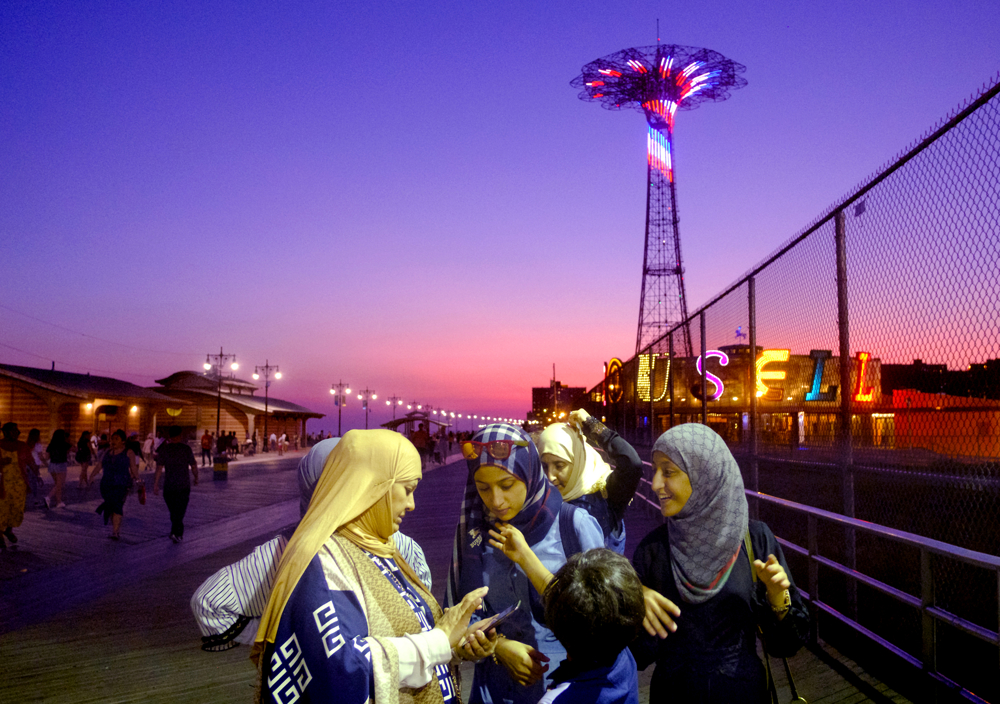 Boardwalk Evening Fun - A family enjoys a summer evening on the Coney Island boardwalk.  Sunday September 24, 2017. Brooklyn, NY, USA