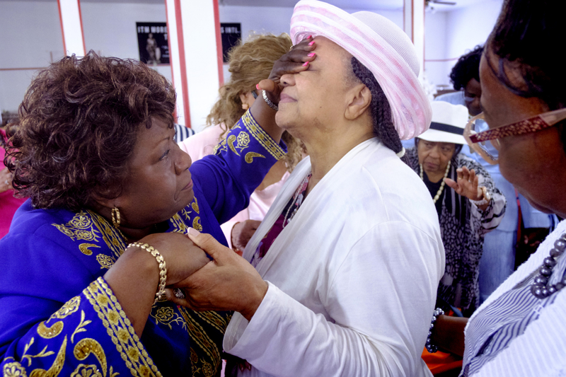 Praying for Health - Church elder Janie Simpson, left, and also the wife of pastor Thomas E. Simpson, Sr., prays for Winnie Lynn who was sick, after the service at the Intercessory Tabernacle church. The church is one of the few African American churches that have remained in Lakewood with a number of them being bought out by the growing Orthodox community. Sunday July 23, 2017. Lakewood, NJ, USA