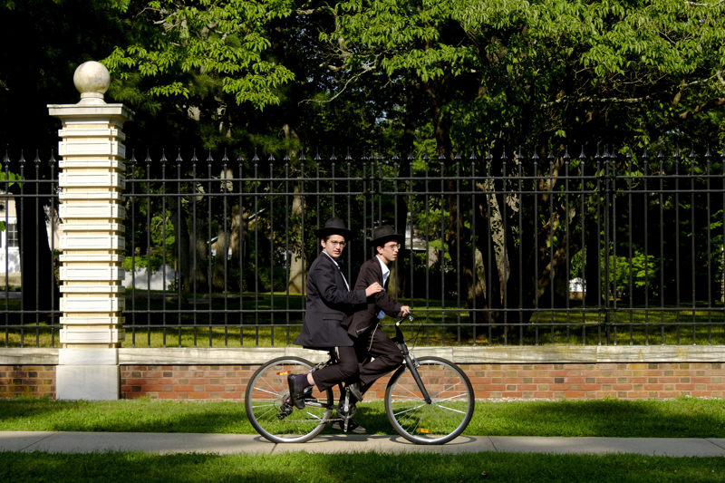 Boys On Bikes - A pair of Orthodox teens share a ride on a bicycle on the sidewalk outside of Georgian Court University. The Catholic university has been good neighbors to Beth Medrash Govoha (BMG) yeshiva since the yeshiva was founded in 1943.   Friday July 21, 2017. Lakewood, NJ, USA