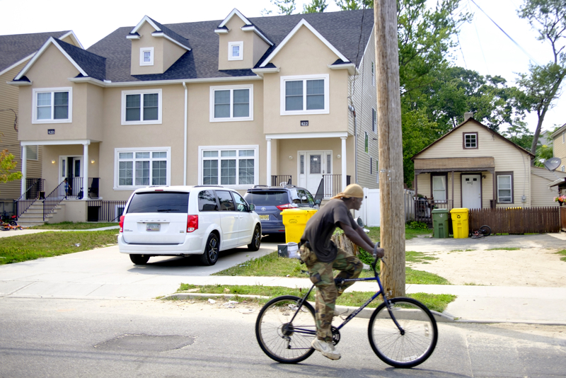 Difference In Houses - A man bikes by new homes that house members of the Orthodox community while a house where a hispanic family stands by next to them along Manetta Avenue.  Thursday July 20, 2017. Lakewood, NJ, USA