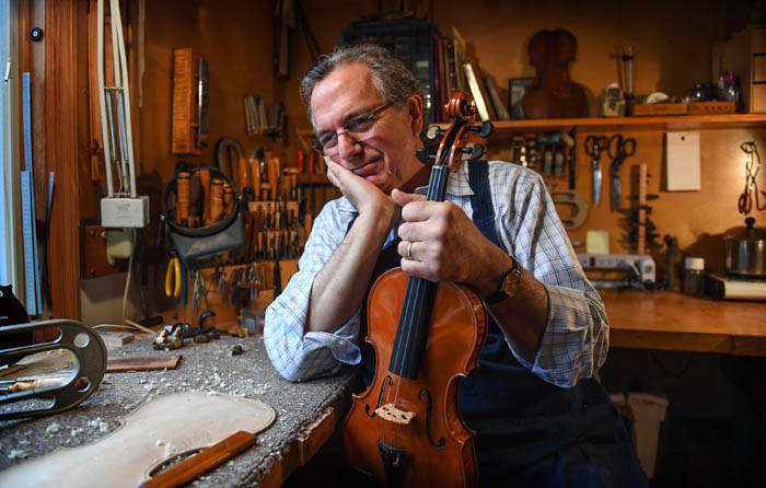 """Portrait of master violin maker Charles Rufino, 66, sitting in the light of a south-facing window at his carpet-covered workbench. His tools surrounding him. """"I'm trying to do this one thing well,"""" he says, """"I enjoy the awareness when I'm working and shaping and cutting the wood. I'm the luckiest man I know."""" April 4, 2018."""