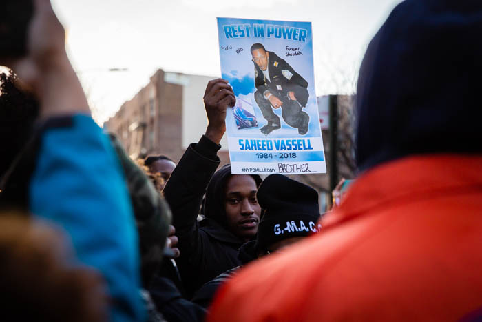 The brother of Saheed Vassell holds up a poster with his image on at the corner of Utica Avenue and Montgomery Street in Crown Heights on April 5, 2018 in New York City, USA.  