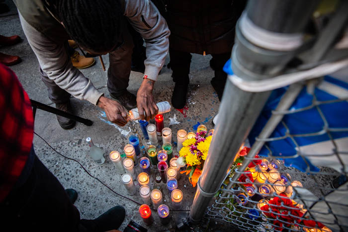 A man lights a candle at a protest held on at the corner of Utica Avenue and Montgomery Street in Crown Heights on April 5, 2018 in New York City, USA.  