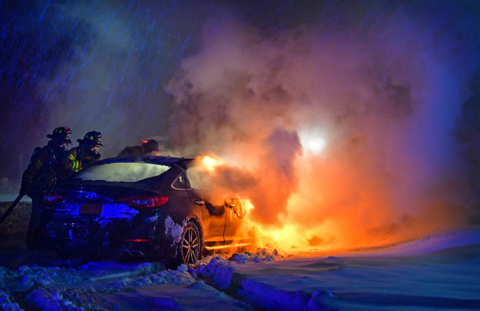 Members of the Ronkonkoma Fire Dept. brave a driving snow storm to battle a fully involved car fire on the north service road of the Long Island Expressway in Holbrook New York, on the evening of March 7, 2018.