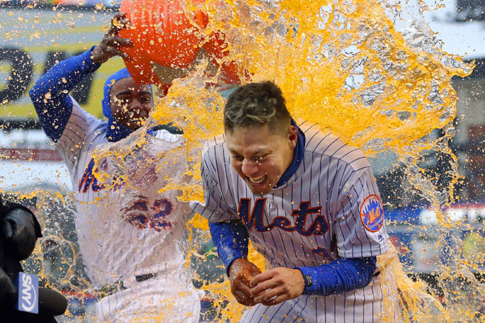 Apr 15, 2018; Queens, NY, USA; New York Mets first baseman Wilmer Flores is doused by left fielder Yoenis Cespedes after hitting a walk off solo home run against the Milwaukee Brewers in the bottom of the ninth inning at Citi Field.