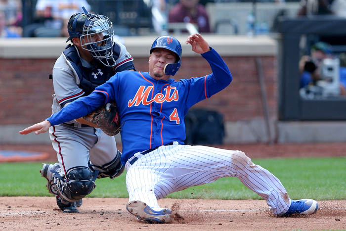 Aug 5, 2018; Queens, NY, USA; New York Mets first baseman Wilmer Flores (4) is tagged out by Atlanta Braves catcher Kurt Suzuki (24) as he tries to score on a fielder's choice by right fielder Jose Bautista (not pictured) during the sixth inning at Citi Field.