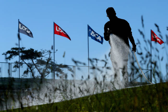 Top golfers from around the world compete in the 2018 US Open from Thursday, June 14 through Sunday, June 17 at Shinnecock Hills Golf Club in Southampton, NY. A course maintenance worker waters the fourteenth hole before the final round. Players had complained all weekend about the dryness of the course.