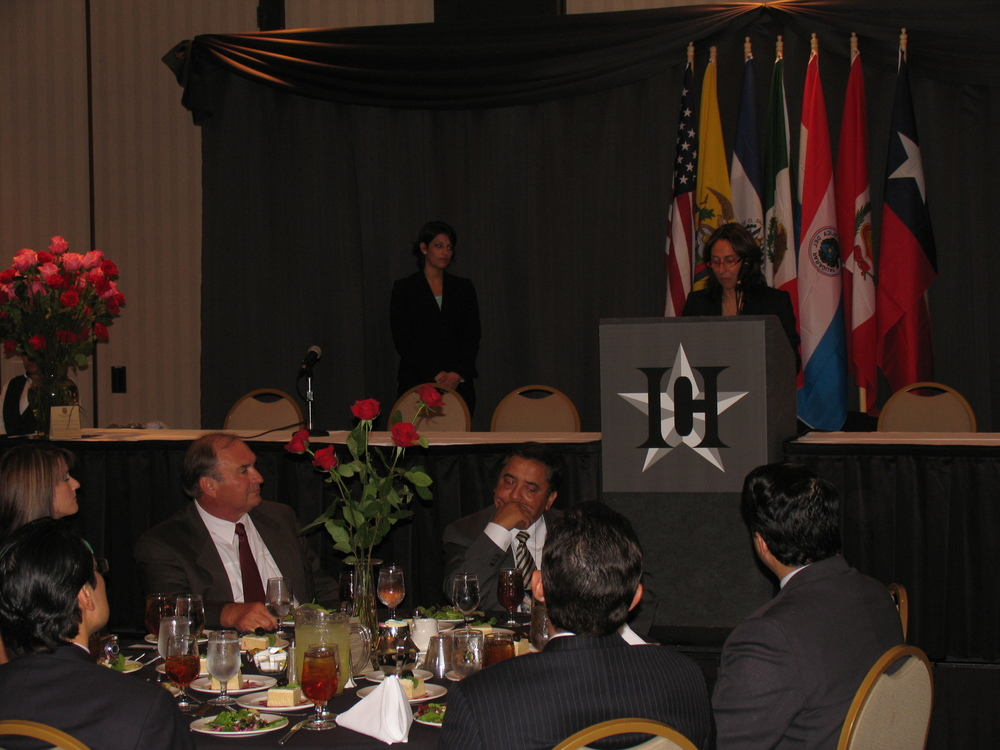 At podium: Patricia Moore, COO Sentrum International, Chair of International Summit  At table: Douglas Faulkner, CEO Faulkner Explorations LLC; H.E. Luis Sándiga, Ambassador, Consul General Peru