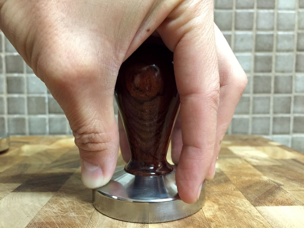 My first tamper, a cheap 58mm with short wood handle. I like the shorter handle so I can equally distribute my fingertips to do an even initial leveling tamp, like pictured.