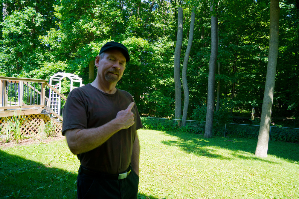 Joe pointing to the wooded hinterland, out back.