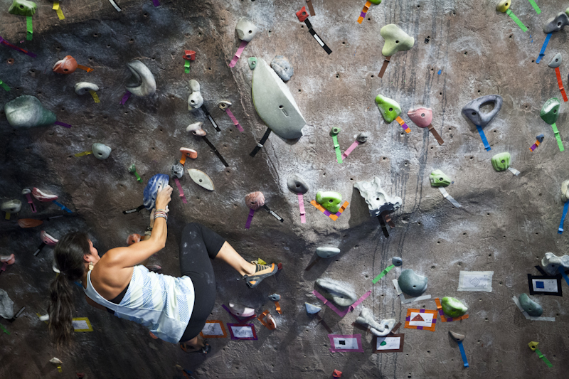 Woman bouldering at indoor climbing gym in Portland, Maine | Photo by Whitney J. Fox Photography