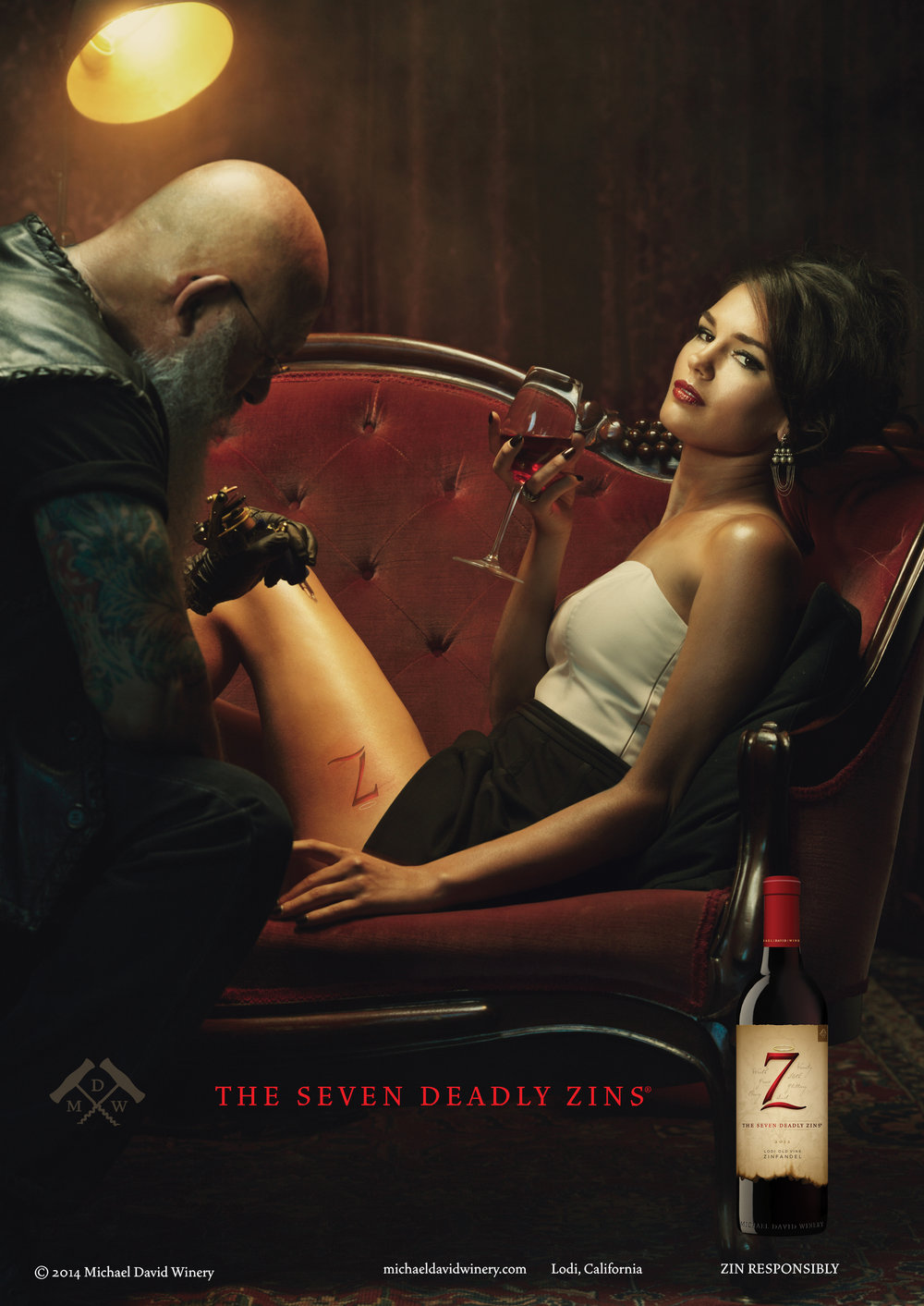 THE SEVEN DEADLY ZINS - We translated naughty into lush, unexpected and inviting for Michael David's flagship brand, The Seven Deadly Zins. The campaign ran in Wine Spectator and Wine Enthusiast magazines, in-store displays, social and as digital media.THE CONCEPTWe see an amazing visual of a beautiful, sensuous woman reclining on a tattoo parlor couch as the artist tattoos the Seven Deadly Zins logo on her thigh. A single bright light illuminates the image and a David Lynchesque red velvet curtain brings the mood even more so into the surreal. The strong visual message of being unconventional, forbidden and sensual differentiates the brand from mundane vineyard-themed wine advertising.THE RESULTSThe Seven Deadly Zins had started small in Lodi with fewer than 25,000 cases. After the relaunch of the packaging and subsequent advertising campaign, the brand grew tenfold. It was named an Impact Hot Brand in 2016, and 7 Deadly Zins is now America's No. 1 Zinfandel by dollar sales
