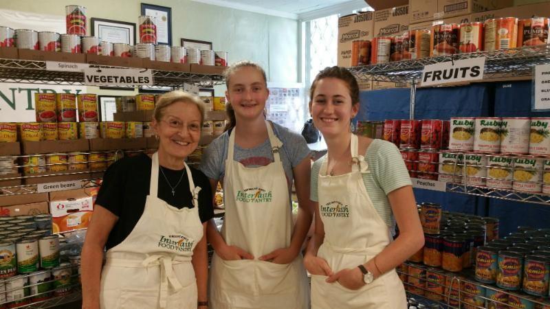 Lynn Harrington,Grace Lunder and Faith Thompson volunteering at the Interfaith Food Pantry.