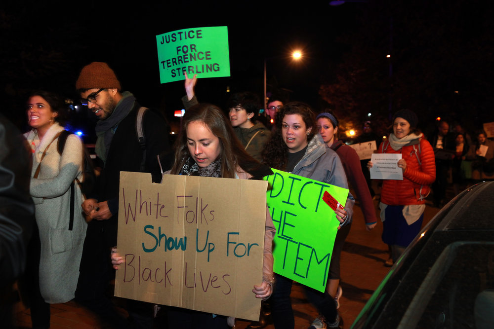 """A multiracial group marches for justice for Terrence Sterling. White woman in foreground carries sign that reads """"White Folks Show Up For Black Lives."""" Photo by Rick Reinhard"""