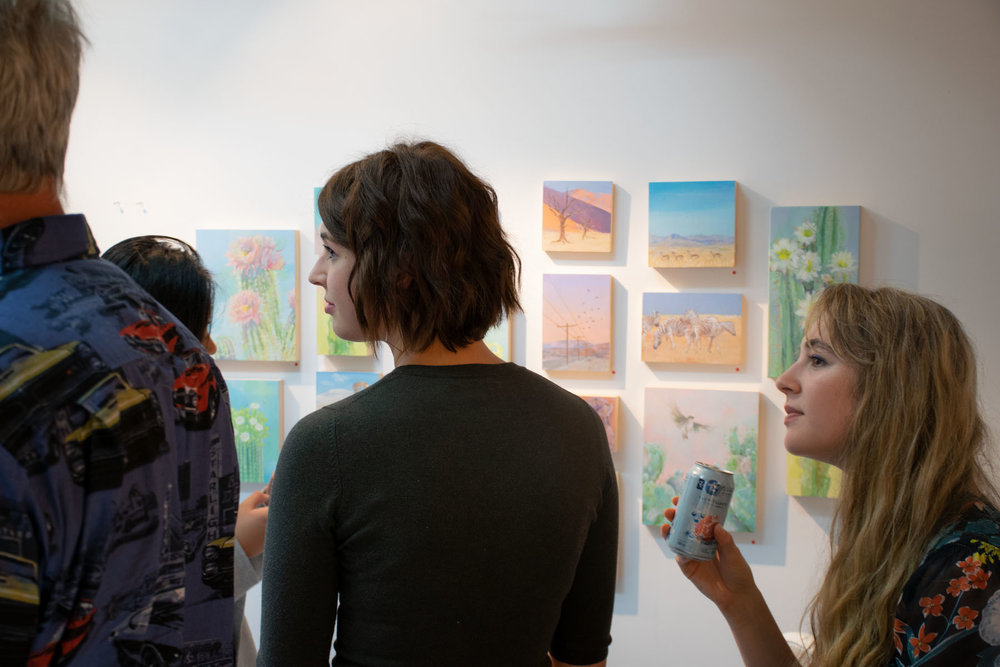 Jominca in front of her paintings during the show