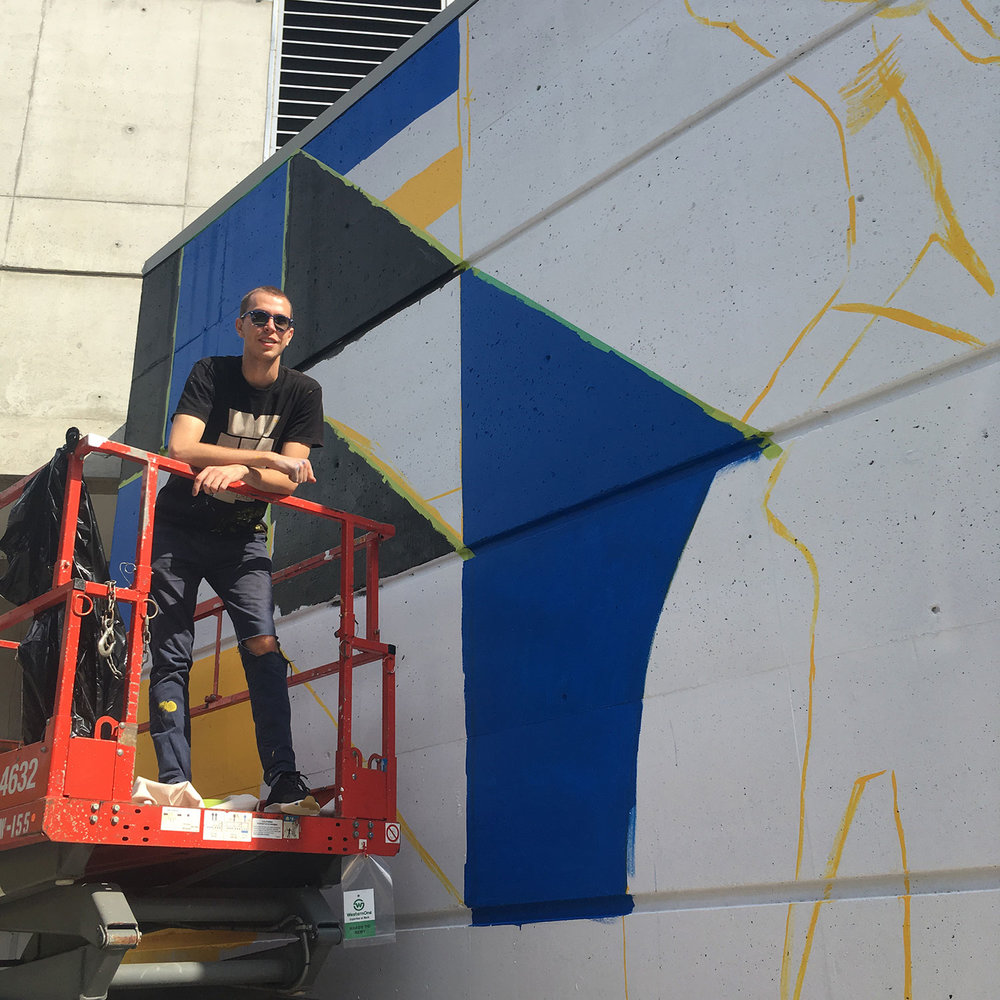 Cristian Fowlie (IDEA Grad 2015) takes a breather during the early stages of his two-sided mural for Birch Building