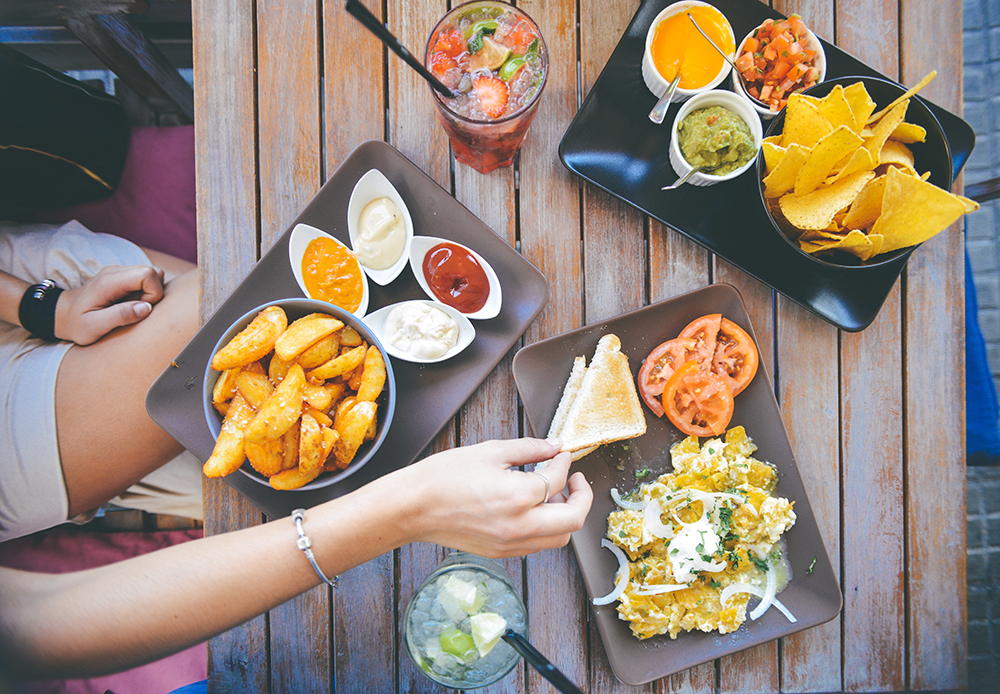 Womans-Hand-Taking-Food-From-Cafe-Table-With-Dips-And-Drinks.jpg