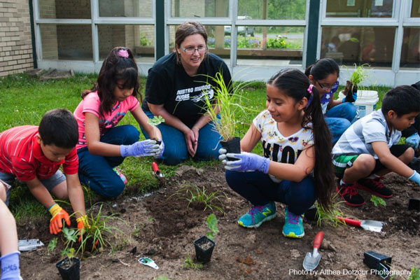 Bryn Scriver, a parent volunteer, assisting students on planting day at Nuestro Mundo Community School's rain garden.   Photo courtesy Althea Dotzour