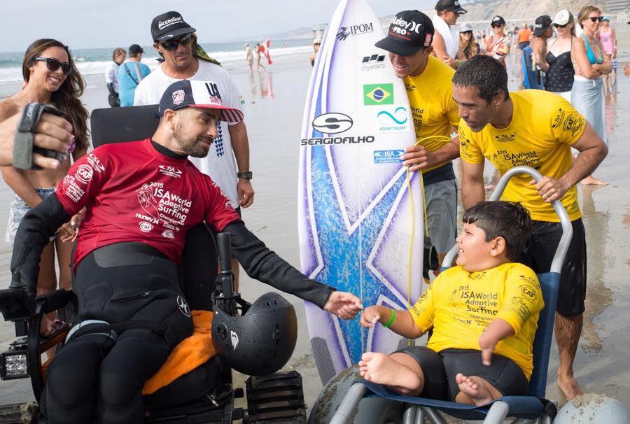 jesse fist bumping little brazilian surfer.jpg