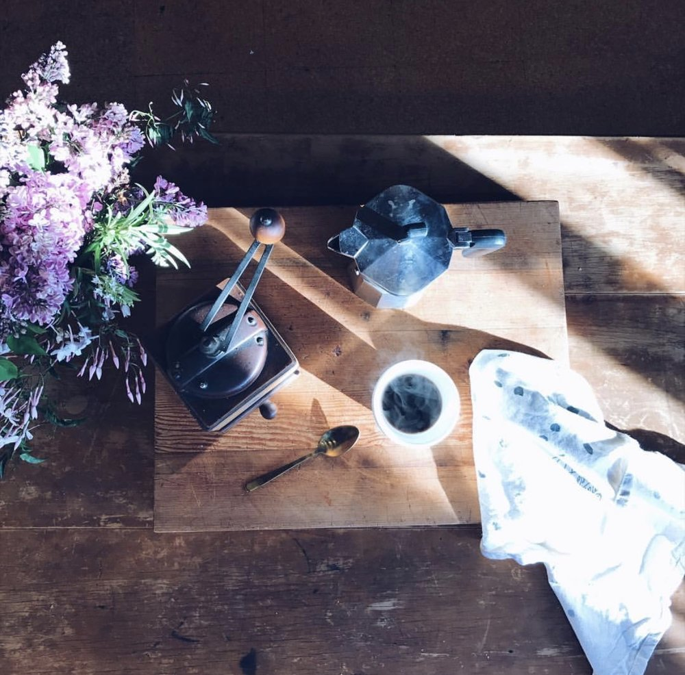 Kate captures impermanence with this beautiful morning coffee situation. The light and shadows will be fleeting, as will the steam from that cup of coffee. The time worn beauty of the table and coffee accessories is unique and can't be reproduced. The fragile nature of the flowers adds to the gentle calm of this image. By  @thisfamilyrobinson