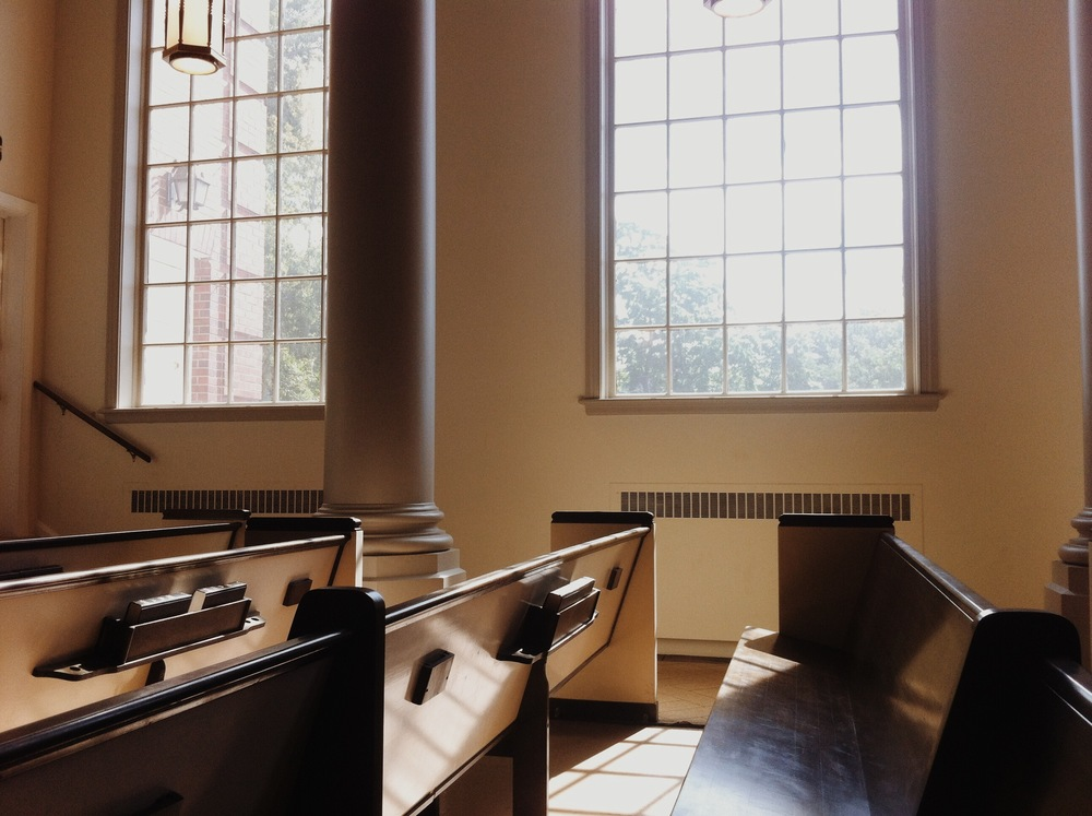 Image of morning sun pouring over pews in a church
