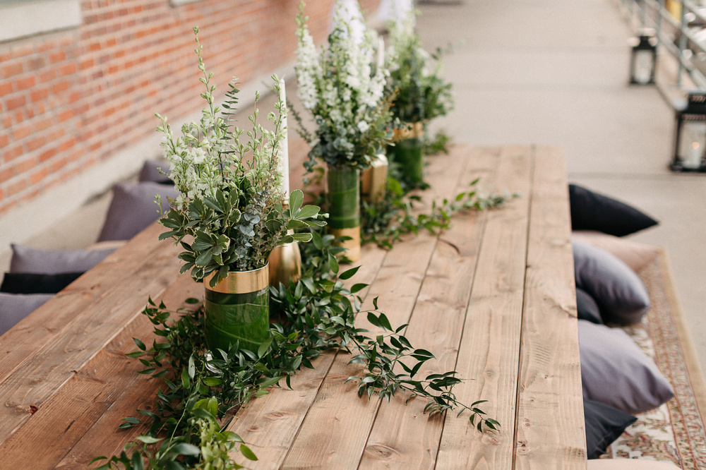 Image of greenery and candles on an empty wooden table