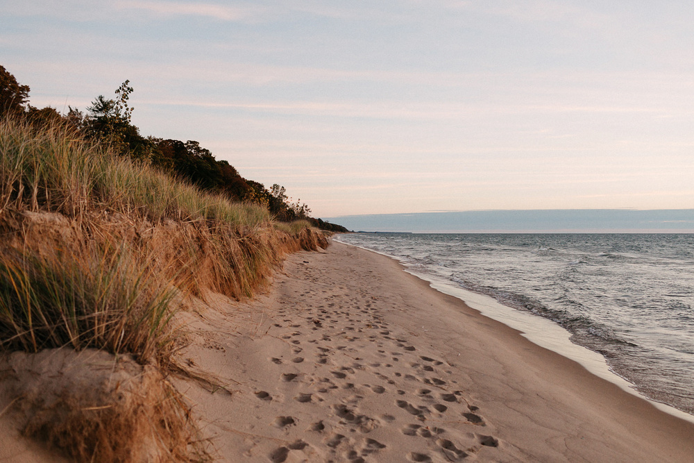 Image of Lake Michigan beach at golden hour, footsteps in the sand, water rushing to the shore.