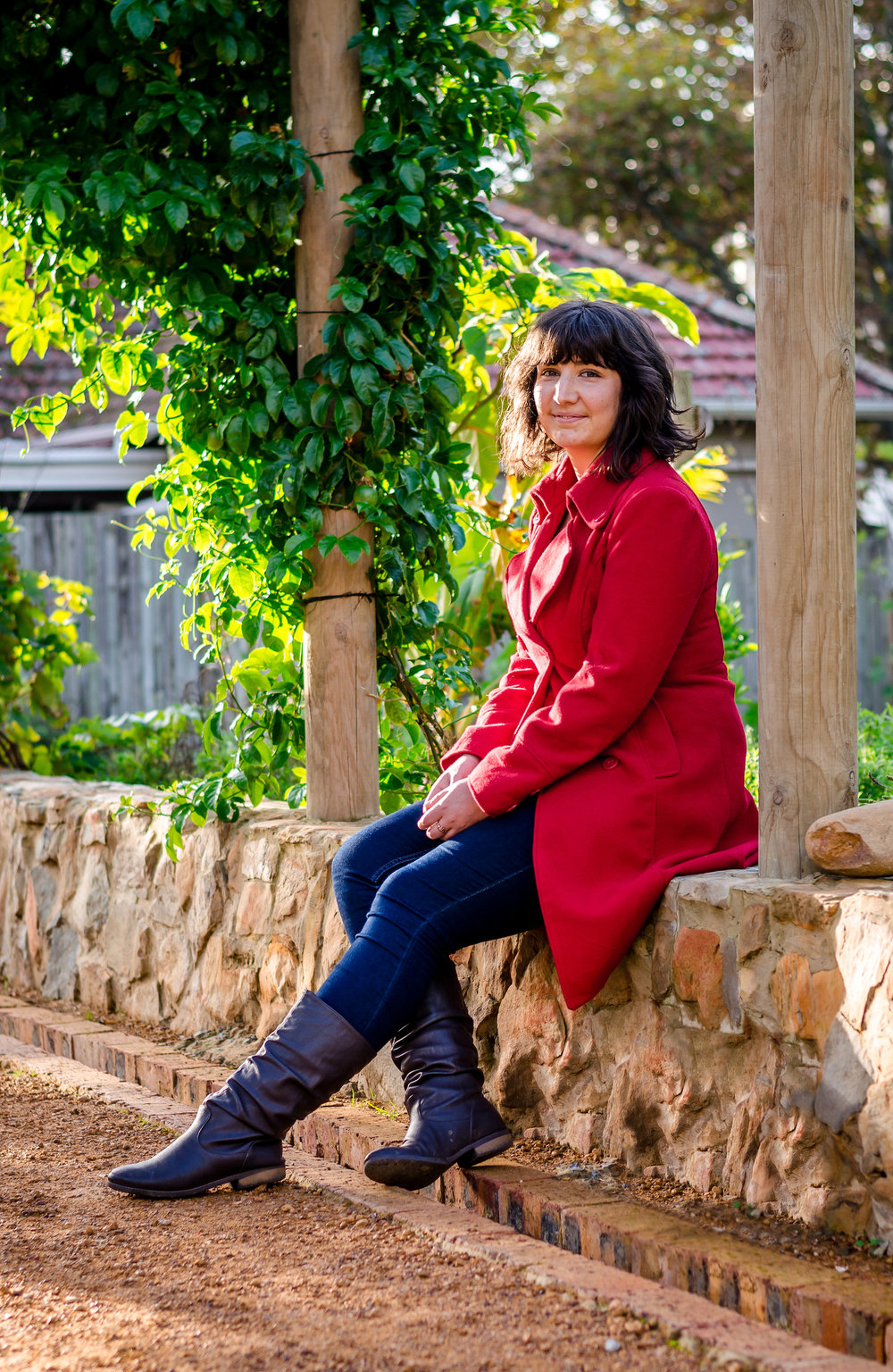 Image of Amy, Of Larks contributing writer, sitting on the edge of a garden wall.
