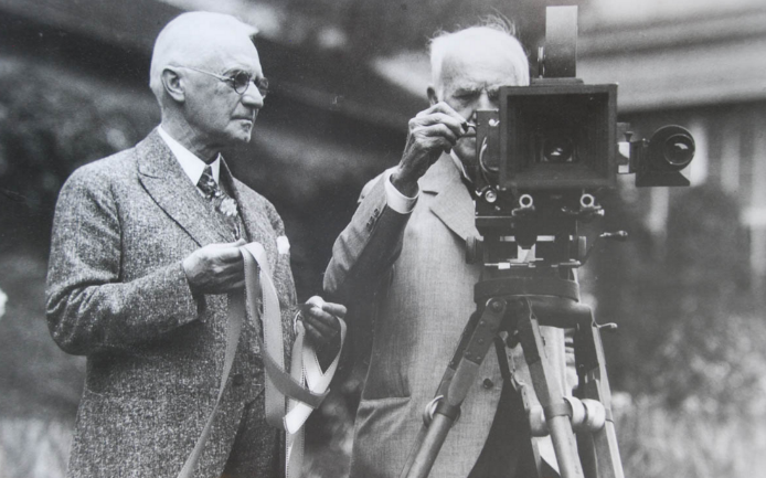 George Eastman (left) feeding film to a camera with Thomas Edison (right).