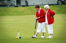 Senior women playing croquet