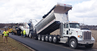 Photo of construction vehicle and crew paving a roadway.