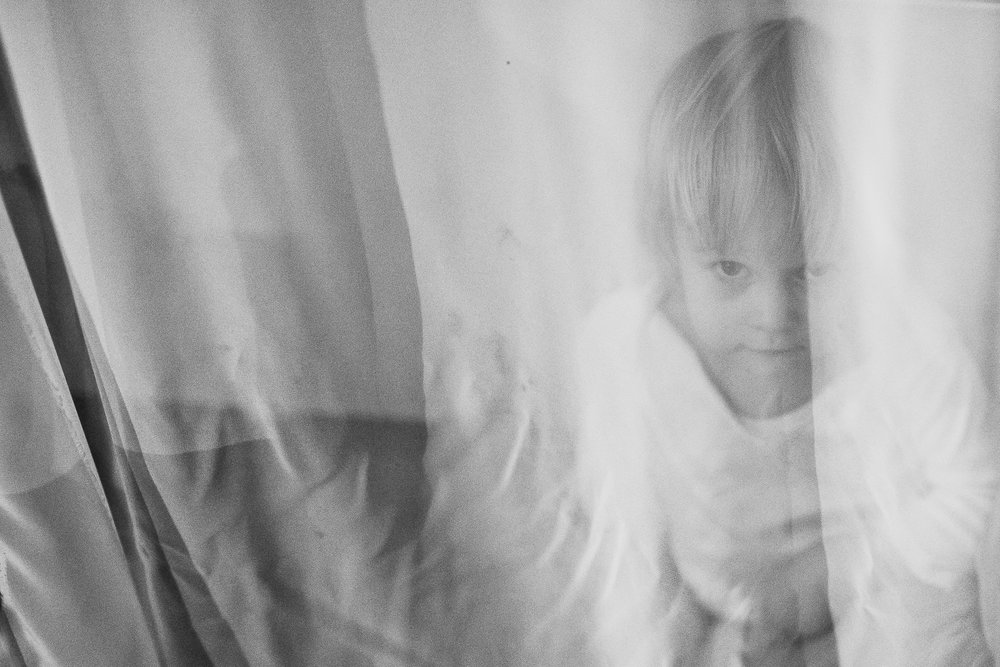 Child behind curtains