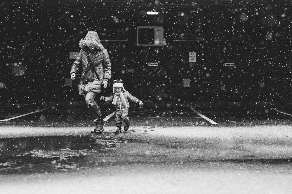 Child and mother running between snowflakes