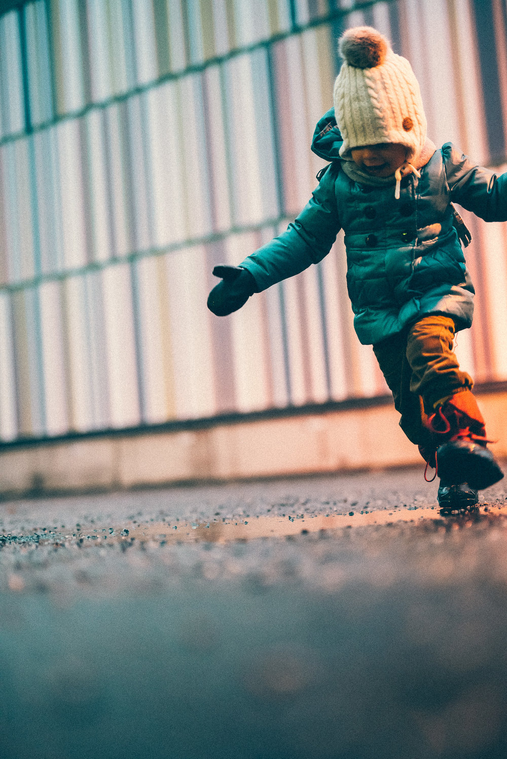 Child running through a puddle in parking lot