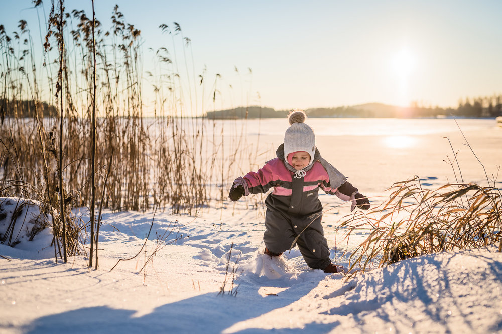 Toddler walking in the snow in winter sun