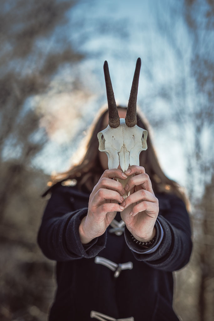 Teenager holding horn of deer or mask in front of head
