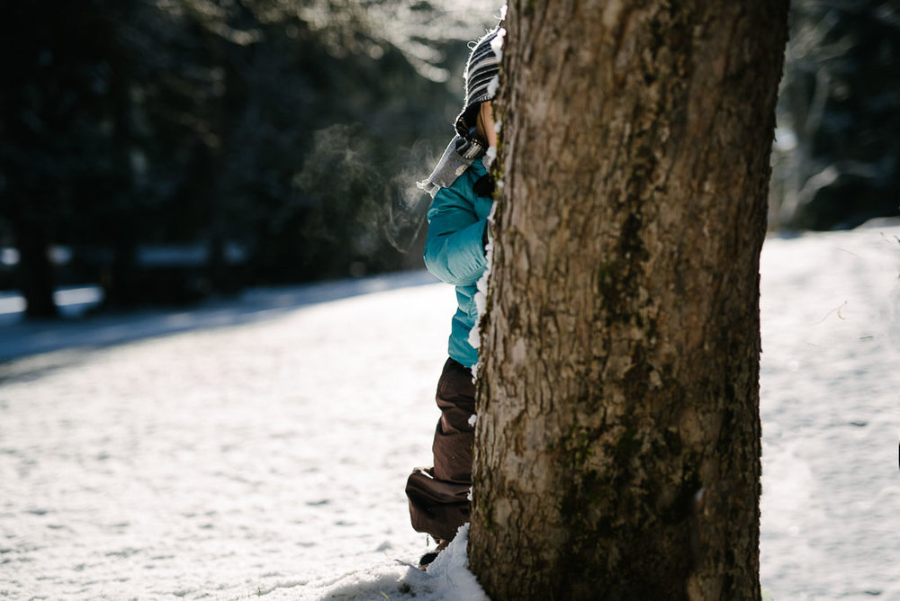 Child hiding behind a tree in winter with breath vapor visible