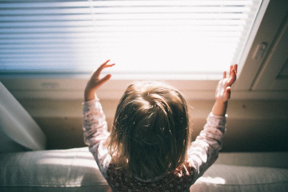 child in window light